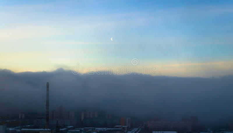 Облако загрязнения тумана и смога покрывает город сверху ясное небо и луна стоковые фотографии rf
