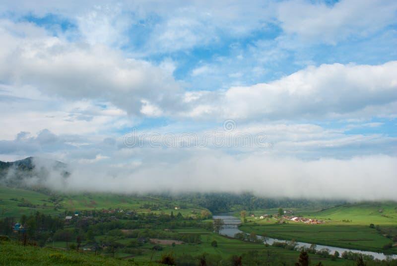 Облако над деревней утро лужка тумана над водой Гигантское облако Деревня в горах Карпатов стоковые фото