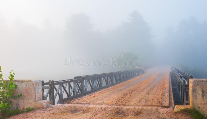 Облако нижнего яруса в дороге майны яркого тумана одиночных, стали & мосте тимберса в исчезая лес стоковые фотографии rf