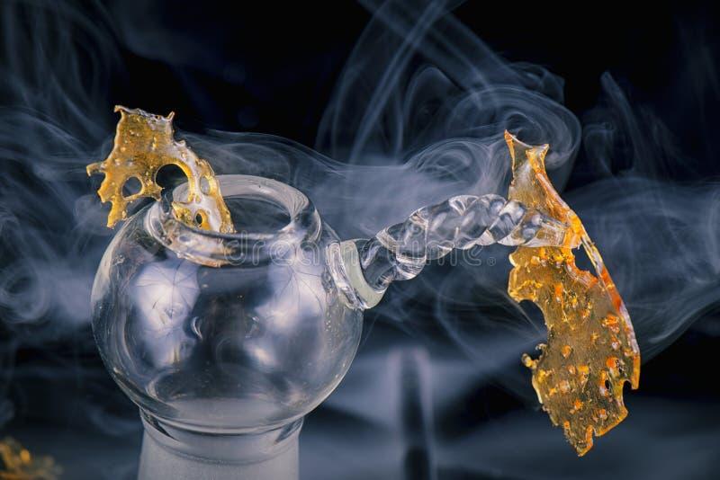 Обломок концентрата масла марихуаны aka изолированный с стеклянным снаряжением стоковое изображение rf