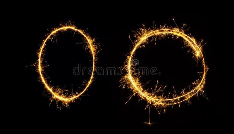 Овал и круг бенгальского огня изолированные на черной предпосылке стоковая фотография
