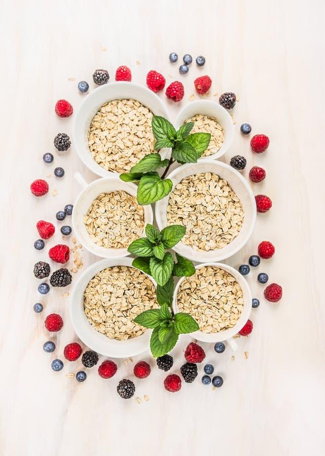 Овес шелушится куча в белых шарах с пиперментом и свежими ягодами стоковое изображение