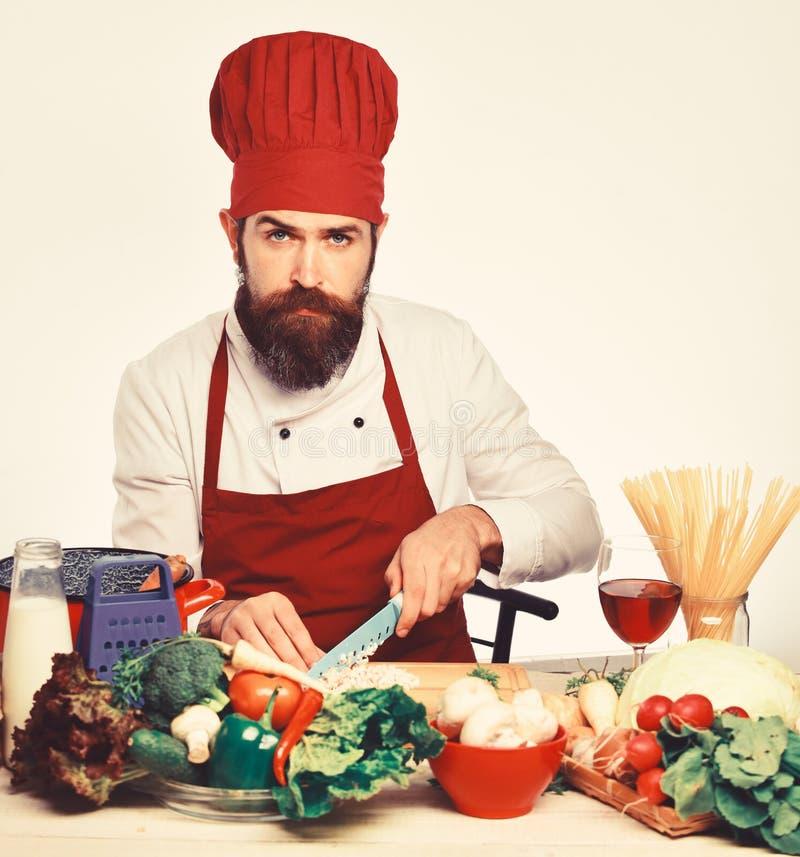 Овощи вырезывания человека шеф-повара для салата Кашевар в красной форме стоковые изображения rf