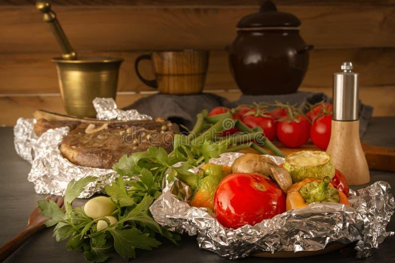 Овощи испеченные в стоге фольги и мяса на деревянном столе со свежими томатами и зеленых цветах на предпосылке деревенских утваре стоковое изображение rf