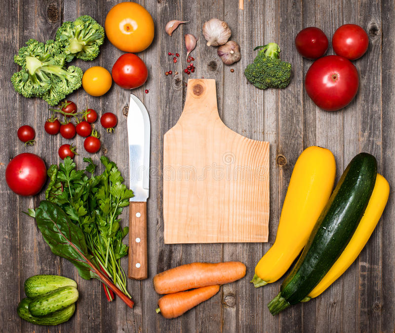 Овощи и ингридиенты для варить вокруг разделочной доски на r стоковые фотографии rf