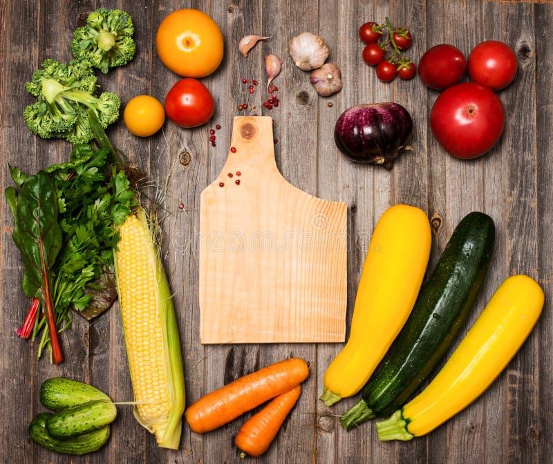 Овощи и ингридиенты для варить вокруг разделочной доски на r стоковая фотография