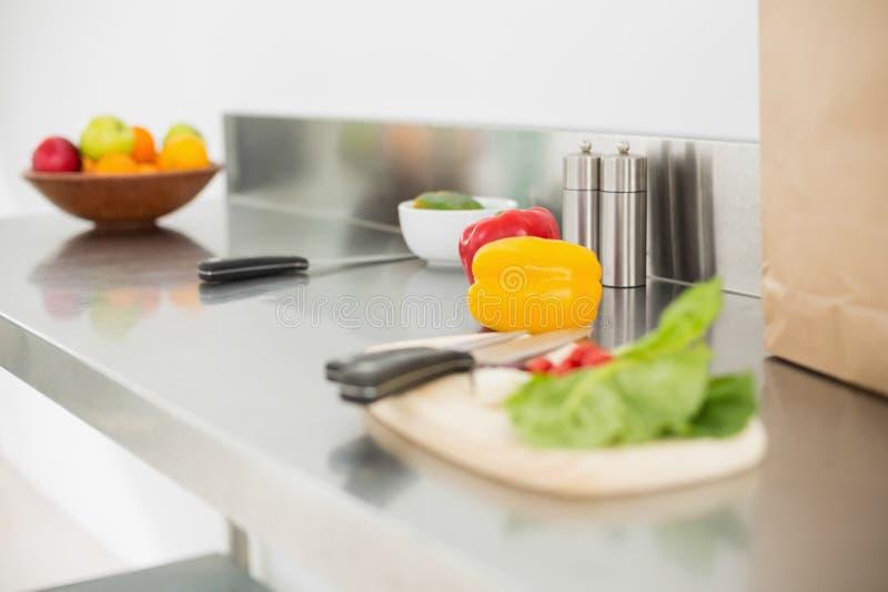 Овощи и прерывая доска на счетчике хрома стоковая фотография rf