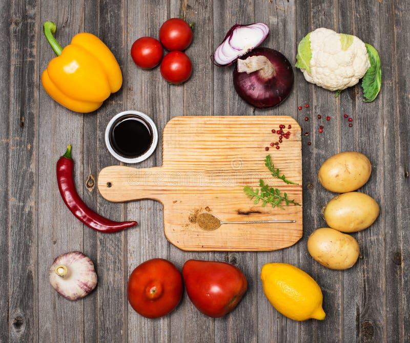 Овощи и специи и пустая старая разделочная доска Красочное ingr стоковая фотография rf