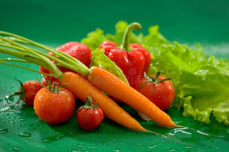 Овощи - моркови с верхними частями, красными томатами, красным болгарским перцем, паприкой, зеленым салатом стоковые фото