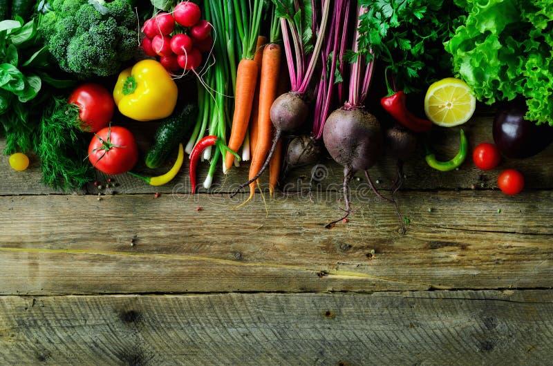 Овощи на деревянной предпосылке Био здоровые натуральные продукты, травы и специи Сырцовая и вегетарианская концепция ингридиенты стоковая фотография
