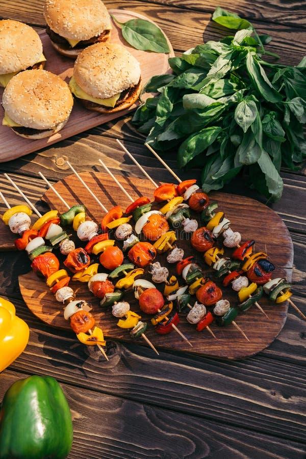 Овощи на протыкальниках и гамбургерах сварили outdoors на гриле стоковое изображение rf