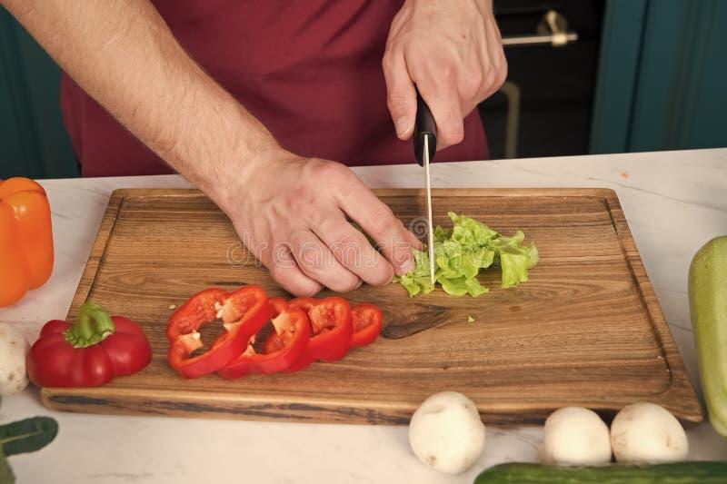 Овощи получая отрезок на деревянной разделочной доске Салат куска руки зеленый с керамическим ножом Руки отрезали овощи с стоковая фотография rf
