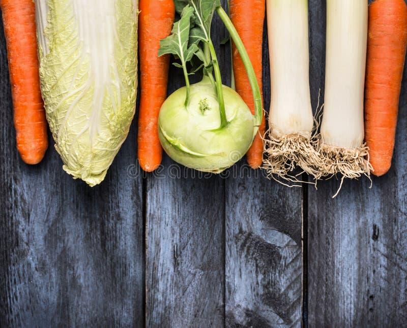 Овощи различные для варить: лук-порей, Kolrabi, капуста и моркови на голубой деревянной предпосылке, взгляд сверху стоковое изображение rf