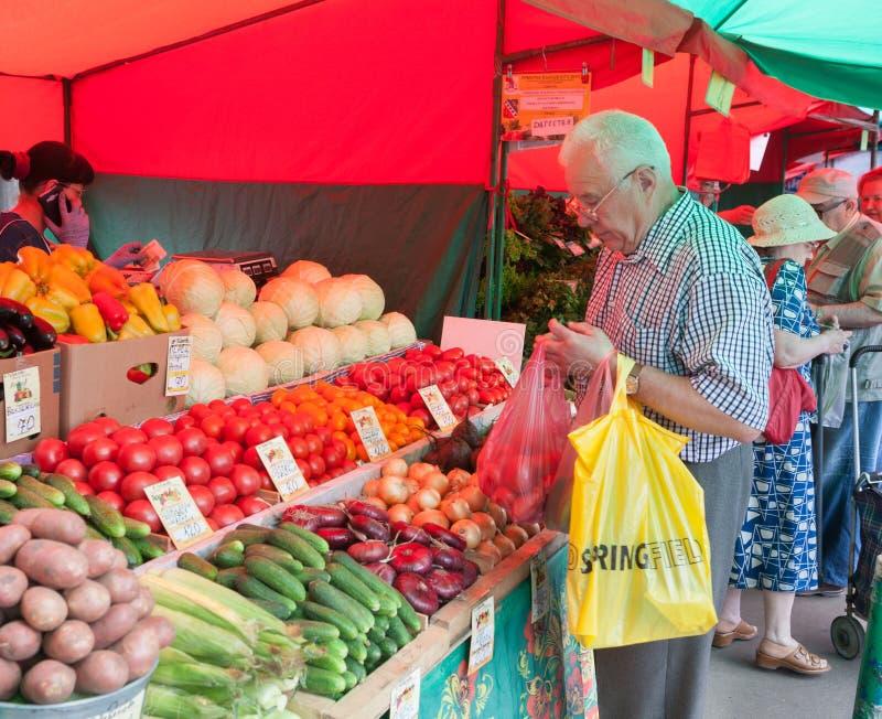Овощи старшего человека покупая в Vegetable ярмарке стоковые фотографии rf