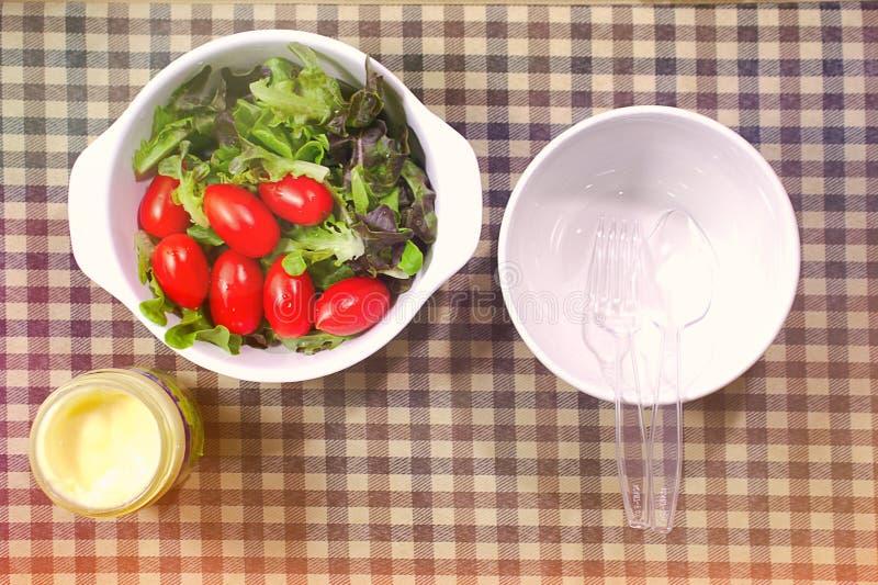 Овощи томата в шаре заправок для салата и шаров на плите еды стоковые изображения