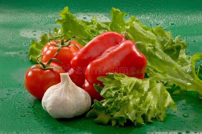 Овощи - томаты, чеснок, красный болгарский перец, листья салата стоковая фотография