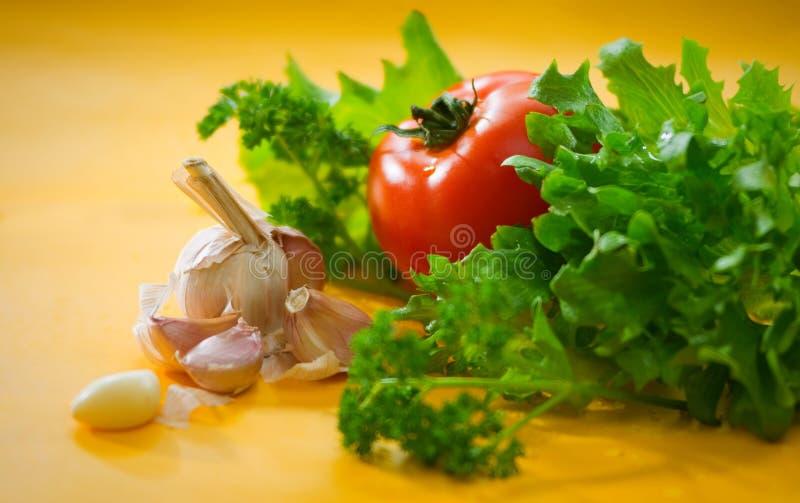 Овощи - томат, чеснок, зеленый салат, петрушка стоковое фото