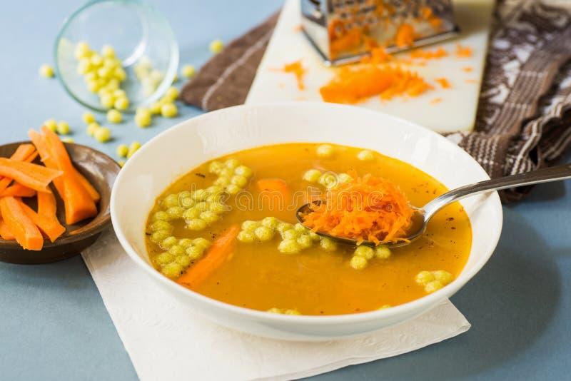 Овощной суп с заскрежетанной сырцовой морковью на ложке стоковое изображение rf
