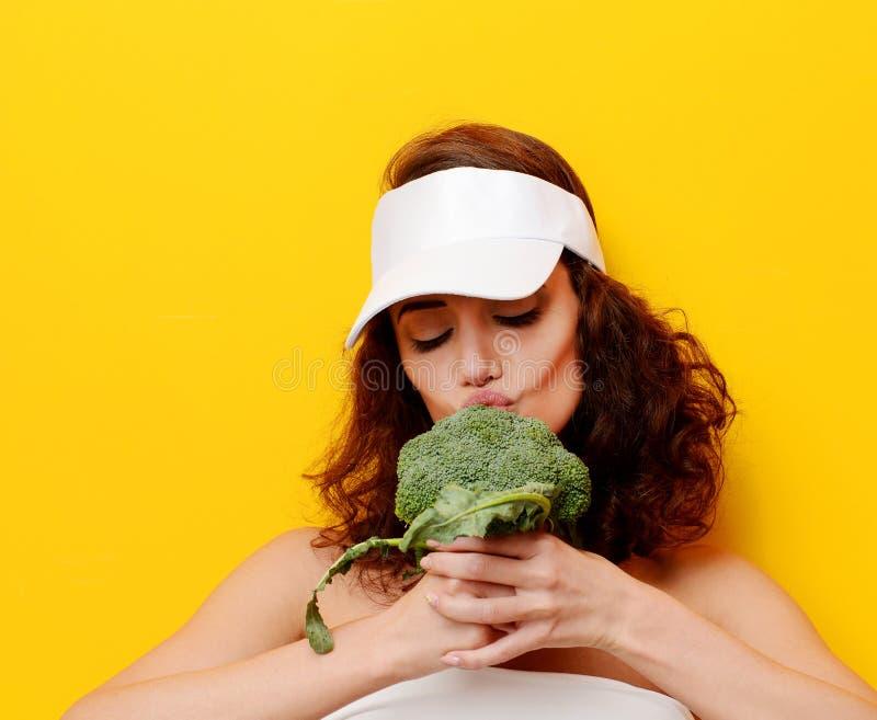 Овощ брокколи укуса молодой женщины большой свежий зеленый в белой шляпе стоковые фото