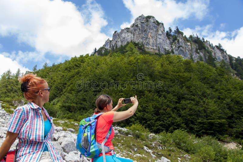 2 довольно женских женщины фотографируя selfie на горном пике стоковые фото