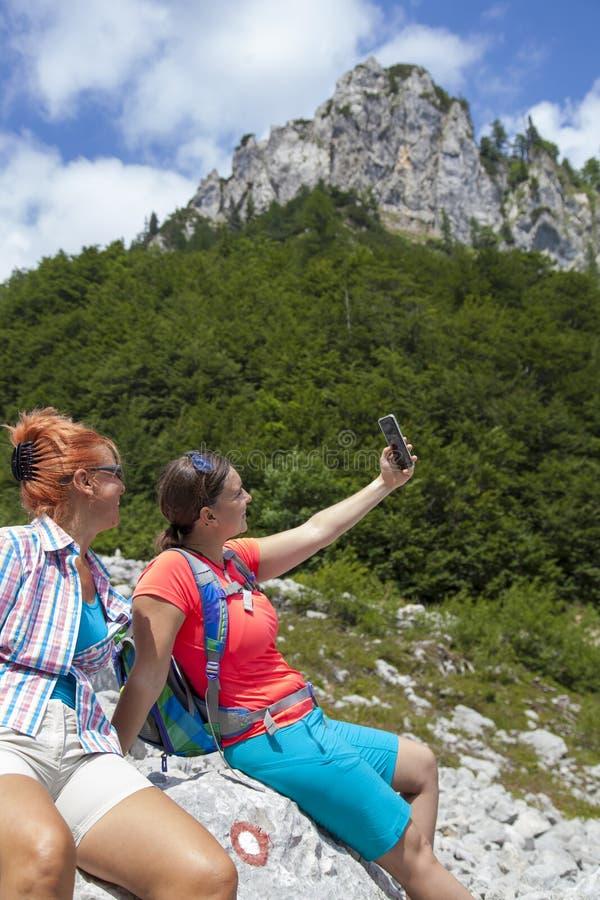 2 довольно женских женщины фотографируя selfie на горном пике стоковая фотография
