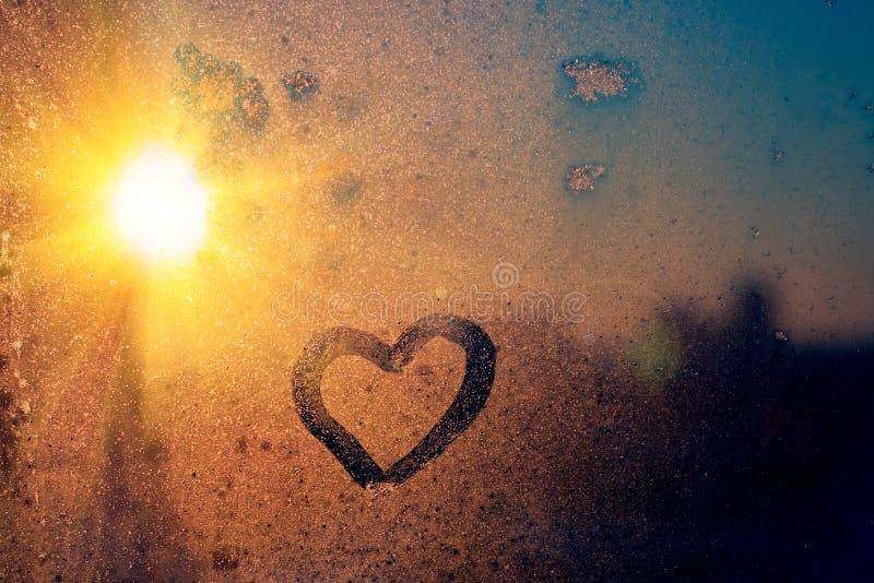 Оглушать винтажный янтарный свет восхода солнца с надписью любов сердца на замороженном стекле окна r E стоковые фотографии rf