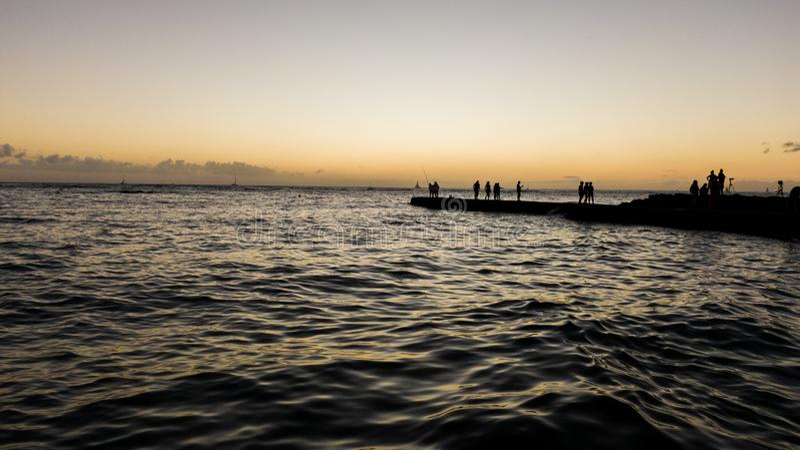 Оглушать воздушный взгляд трутня вскоре после захода солнца показывая пристань/молу на пляже Waikiki Туристы и стоять и admir рыб стоковые фотографии rf