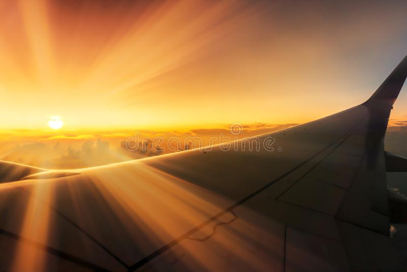 Оглушать восход солнца путешествуя над облаками на самолете с солнечными лучами над крыльями через окно стоковая фотография