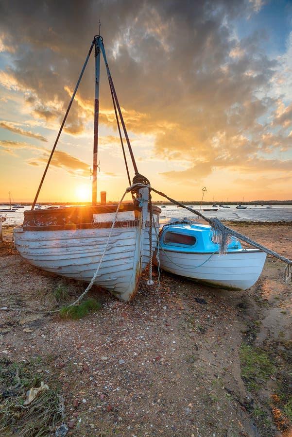 Оглушать заход солнца над старыми рыбацкими лодками на береге на западном Mersea стоковые изображения rf