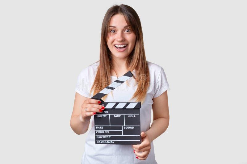 Оглушая радостный кавказский женский директор держит clapperboard создания фильма, подобия для того чтобы завоевать успех в снима стоковое изображение