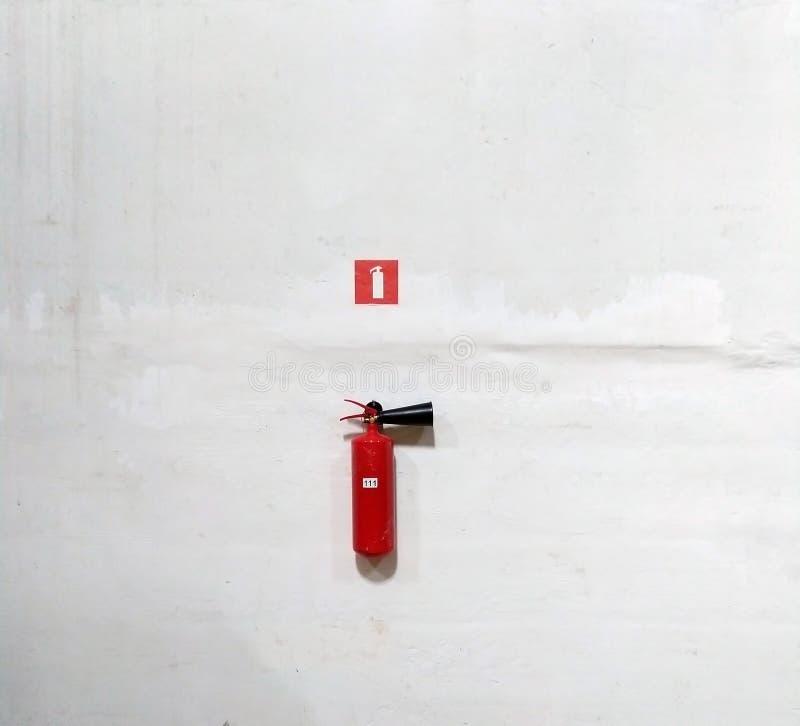Огнетушитель на белой стене, готова к использованию стоковые изображения rf