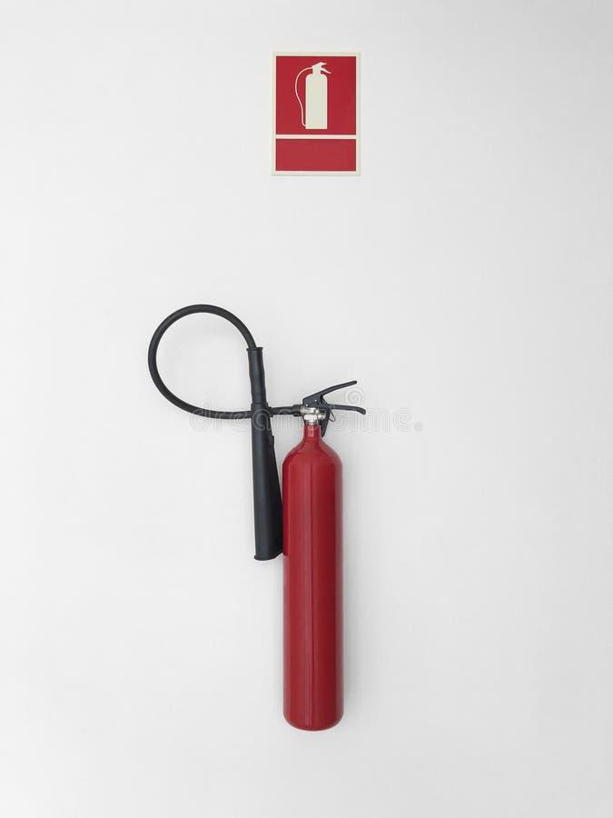 Огнетушитель с сигналом тревоги знака на белой стене стоковая фотография