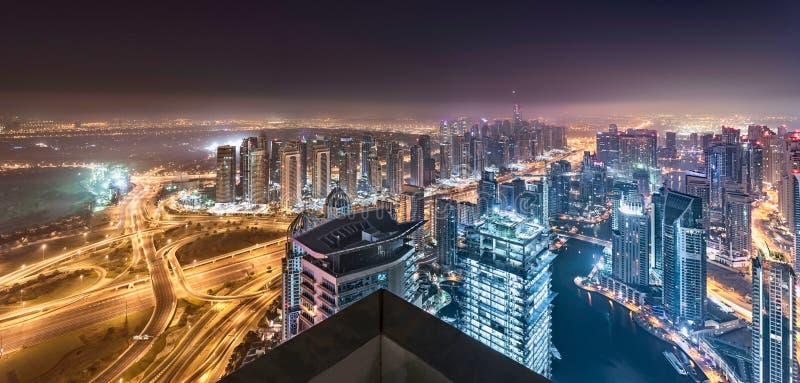 Огни горизонта Дубай накаляя в мглистой ноче с красивым панорамным взглядом крыши башен стоковые фото
