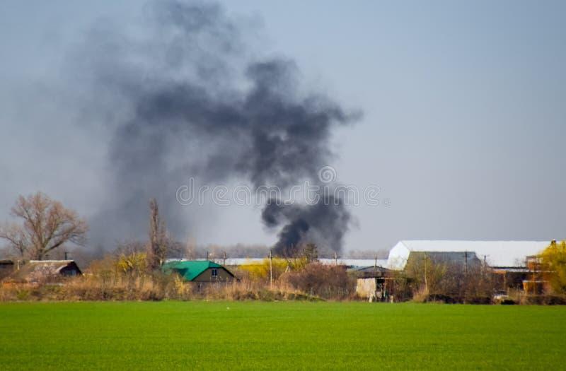 Огонь и черный дым вне деревни Сажа от стоковое изображение rf