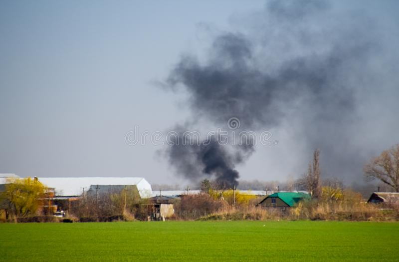 Огонь и черный дым вне деревни Сажа от стоковая фотография rf