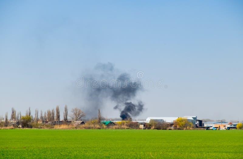 Огонь и черный дым вне деревни Сажа от стоковые изображения