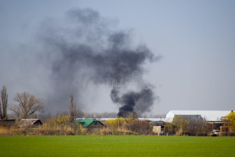 Огонь и черный дым вне деревни Сажа от гореть стоковое фото rf