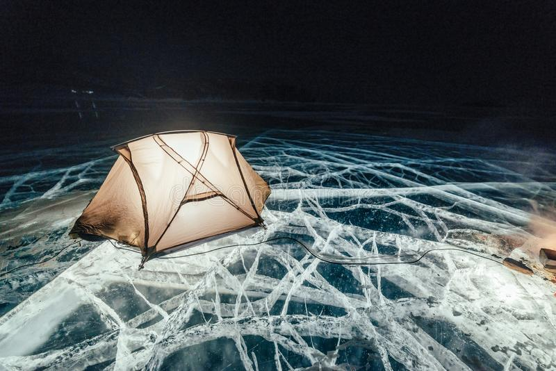 Огонь на льде вечером Кемпинг на льде Шатер стоит рядом с костром озеро baikal Рядом автомобиль Шатер укрытия и иллюстрация вектора