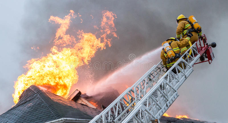 Огонь дома сражения пожарных пылая стоковые изображения rf