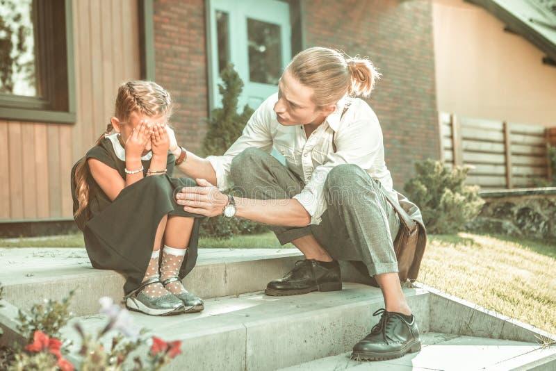 Огорченная длинн-с волосами маленькая девочка закрывая ее разрывы с ладонями стоковые фотографии rf