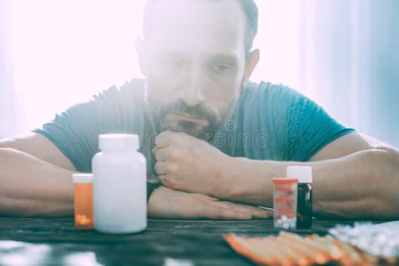 Огорченный расстроенный человек принимая разные виды таблеток стоковые фото