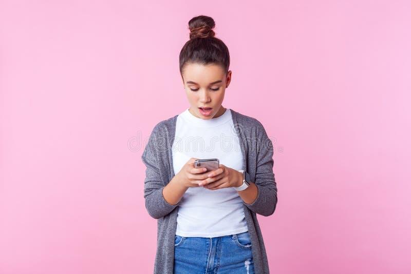 Ого, потрясающее мобильное приложение! Портрет девушки брюнетки, читающей сообщение по телефону с выражением шока розовый фон стоковая фотография