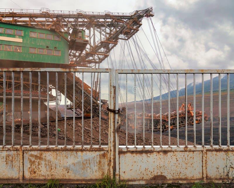Огромная машина угля добычи угля за железным стробом стоковые изображения rf