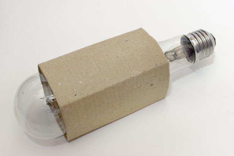 Огромная раскаленная добела электрическая лампочка в рифлёной картонной коробке стоковая фотография