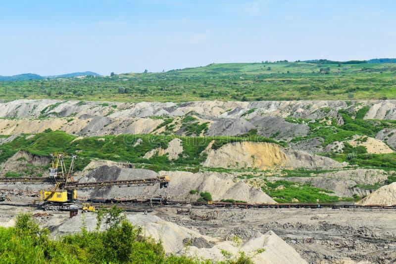 Огромная угольная шахта открытого карьера сделанная с большими экскаваторами, затяжелителями, тележками и штабелируя машинами Тяж стоковые фото
