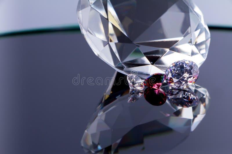 Огромный диамант и несколько шикарных кристаллов на белых поверхност стоковые фото