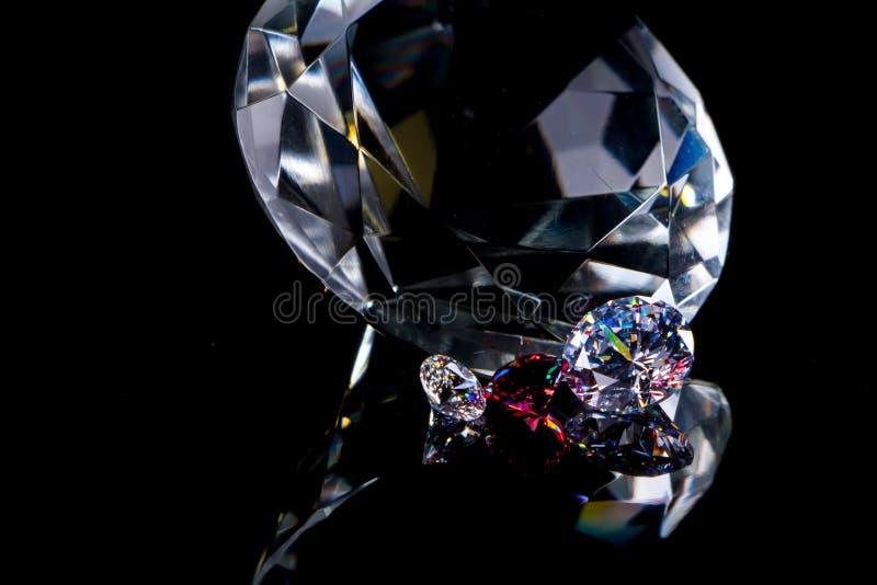 Огромный диамант и несколько шикарных кристаллов на глубоких черных поверхности, shimmer и искре зеркала стоковые изображения