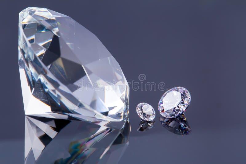 Огромный диамант и несколько шикарных кристаллов на серых поверхност стоковая фотография