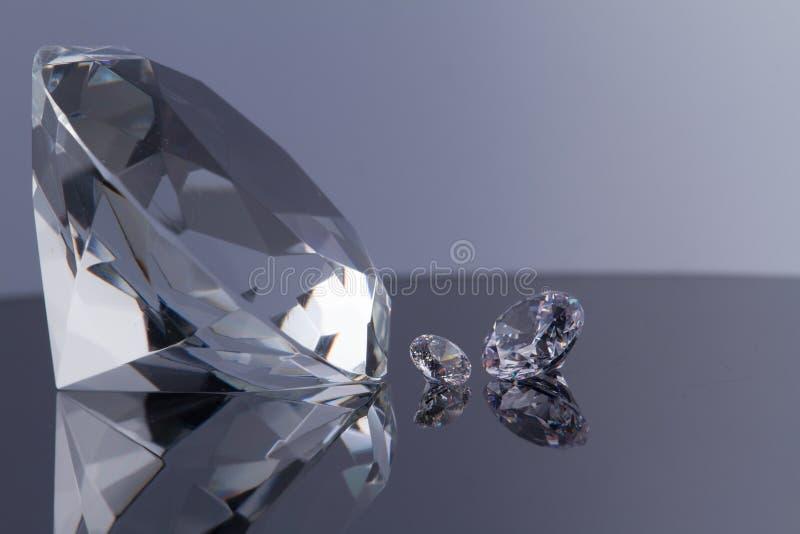 Огромный диамант и несколько шикарных кристаллов на черной поверхнос стоковые изображения