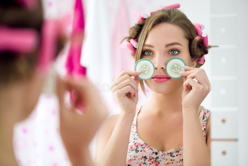 Огурец куска удерживания маленькой девочки для обработки глаз стоковые изображения